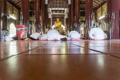 Les gens se sont habillés dans tout le blanc sur le plancher de temple bouddhiste dans la dévotion Images libres de droits