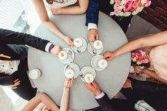Les gens se tenant dans des tasses de mains avec le coffe Photo stock