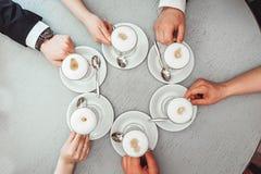 Les gens se tenant dans des tasses de mains avec le coffe Photographie stock libre de droits