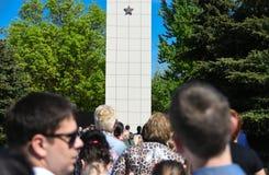 Les gens se tiennent dans la ligne devant le monument sur Victory Day pour étendre des fleurs image libre de droits