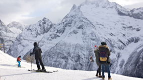 Les gens se tiennent dans la station de sports d'hiver et regardent les montagnes banque de vidéos