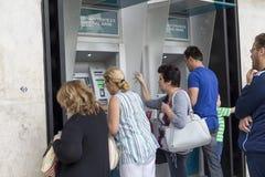 Les gens se tiennent dans une file d'attente pour employer l'ATMs d'une banque Madame de la Grèce Images libres de droits
