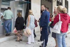 Les gens se tiennent dans une file d'attente pour employer l'ATMs d'une banque Madame de la Grèce Photos stock