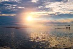 Les gens se tiennent en mer au coucher du soleil en Koh Samui Image libre de droits