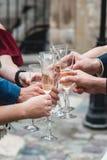 Les gens se tiennent en verres de mains avec du vin blanc Un bon nombre de verres de vin sur la table verte Images stock