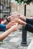 Les gens se tiennent en verres de mains avec du vin blanc Un bon nombre de verres de vin sur la table verte Photographie stock libre de droits