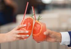 Les gens se tiennent en verres de mains avec le cocktail orange Un bon nombre de verres de vin sur la table verte Image stock