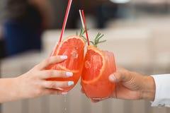 Les gens se tiennent en verres de mains avec le cocktail orange Un bon nombre de verres de vin sur la table verte Images libres de droits