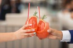 Les gens se tiennent en verres de mains avec le cocktail orange Un bon nombre de verres de vin sur la table verte Photos libres de droits