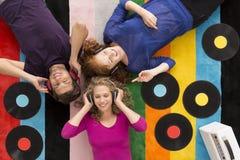 Les gens se trouvant sur le tapis et écoutant la musique Photographie stock