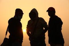 Les gens silhouettent dans l'ensemble de Sun Photos stock