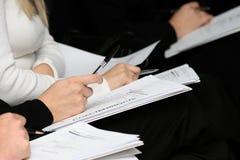 Les gens sont aux conférences avec des stylos et des carnets photo libre de droits