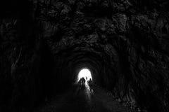Les gens sont dans un tunnel foncé en silhouettes de roche sur une lumière b image stock