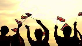 Les gens soulevant les drapeaux nationaux britanniques banque de vidéos