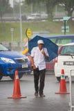 Les gens sous la mousson pleuvoir dans Kuching, Bornéo, Malaisie Photos stock