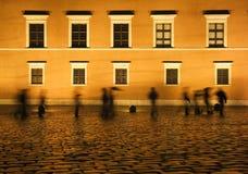 Les gens sous la pluie la nuit Photographie stock libre de droits