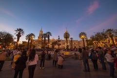 Les gens sur la place principale et la cathédrale au crépuscule, Arequipa, Pérou Image libre de droits