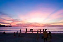 Les gens sur la plage de coucher du soleil Photo libre de droits
