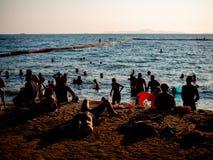 Les gens sur la plage sur le coucher du soleil photo stock