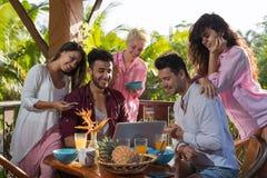 Les gens sur la terrasse d'été ayant l'ordinateur portable, la femme et l'homme d'utilisation de petit déjeuner mangent parler da Images libres de droits