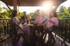 Les gens sur la terrasse d'été ayant le petit déjeuner ensemble, la femme et l'homme mangent parler dans la lumière naturelle de  Images libres de droits