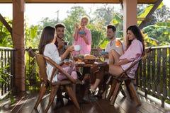 Les gens sur la terrasse d'été ayant le petit déjeuner ensemble, la femme et l'homme mangent parler dans la lumière naturelle de  Image libre de droits