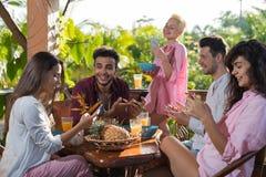 Les gens sur la terrasse d'été ayant les téléphones, la femme et l'homme futés de cellules d'utilisation de petit déjeuner mangen Photo stock