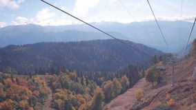 Les gens sur le paysage de télésiège et de montagne avec les arbres colorés banque de vidéos