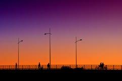 Les gens sur le pont dans le coucher du soleil Image libre de droits