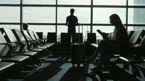 Les gens sur le terminal d'aéroport attendent le vol Utilisez les dispositifs, regardant par les fenêtres à l'aérodrome et Photo stock