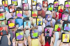 Les gens tenant des comprimés devant les visages Images stock