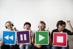 Les gens tenant des icônes de musique et écoutant la musique Images stock