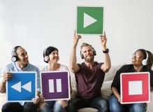 Les gens tenant des icônes de musique se reposant ensemble Images stock