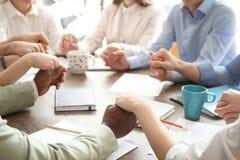 Les gens tenant des mains ensemble à la table Photographie stock libre de droits