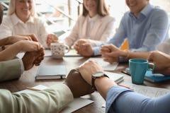 Les gens tenant des mains ensemble à la table Photo stock