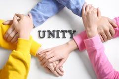 Les gens tenant des mains ensemble autour du mot UNITÉ Image libre de droits