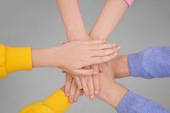 Les gens tenant des mains ensemble sur le fond clair Photographie stock
