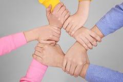Les gens tenant des mains ensemble sur le fond clair Photo stock