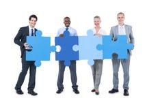 Les gens tenant des morceaux d'un puzzle Photographie stock libre de droits