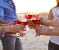 Les gens tenant des verres de vinification rouge un pain grillé à la plage Images stock