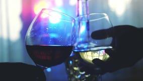 Les gens tenant des verres de vinification un pain grillé dans le mouvement lent sur la table de vacances avec le bokeh de lumièr clips vidéos