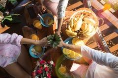 Les gens tenant l'ananas dans des mains ensemble à l'homme et à la femme méconnaissables de Tableau de petit déjeuner dans le mat Photo libre de droits