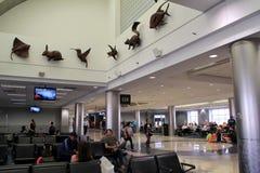 Les gens tenant la porte proche, et assis dans les chaises, embarquement de attente, aéroport de Jacksonville, la Floride, 2015 Photographie stock