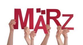 Les gens tenant Word allemand Maerz veulent dire mars Image libre de droits