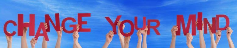 Les gens tenant Word rouge changent votre ciel bleu d'esprit Image libre de droits