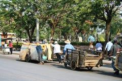 Les gens tirent des chariots sur la route en Thaïlande. Images libres de droits