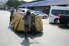 Les gens tirent des chariots sur la route en Thaïlande. Photographie stock