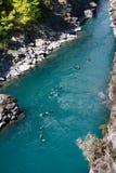 Les gens transportant par radeau le long du fleuve Image libre de droits