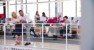 Les gens travaillant aux bureaux dans le bureau ouvert moderne de plan banque de vidéos