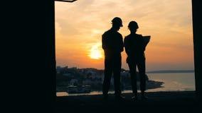 Les gens travaillant avec un modèle sur un fond de coucher du soleil, vue de dos banque de vidéos